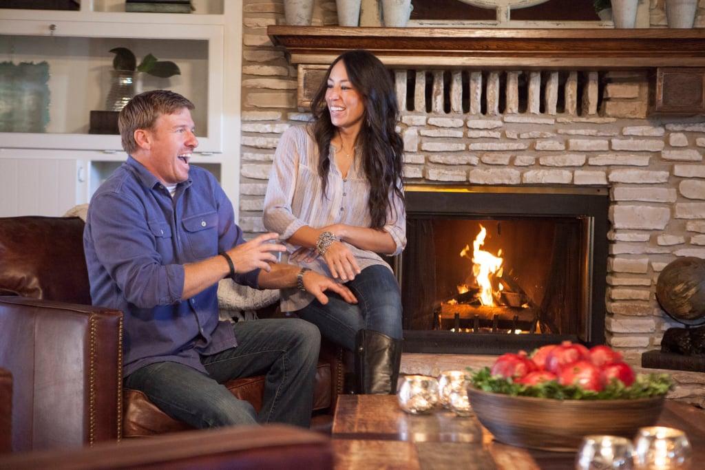 Chip e joanna gaines em sala de estar ao lado de uma lareira, no programa do velho ao novo do discovery h&h