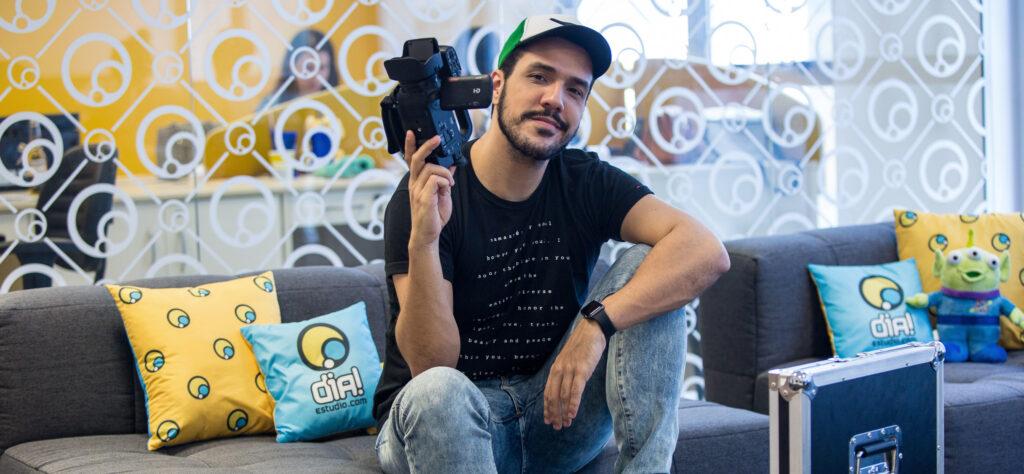 Rafa dias ceo dia estúdio sentado em sofá segurando câmera filmadora