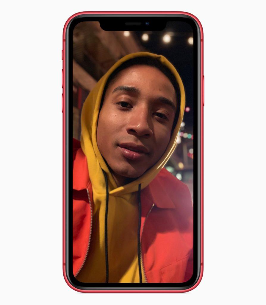 Imagem mostra um iphone xr vermelho exibindo a foto de um jovem negro com a cabeça coberta pelo capuz de um moletom amarelo mostarda e jaqueta vermelha sobreposta. A foto foi tirada usando modo retrato, por isso o fundo está desfocado.