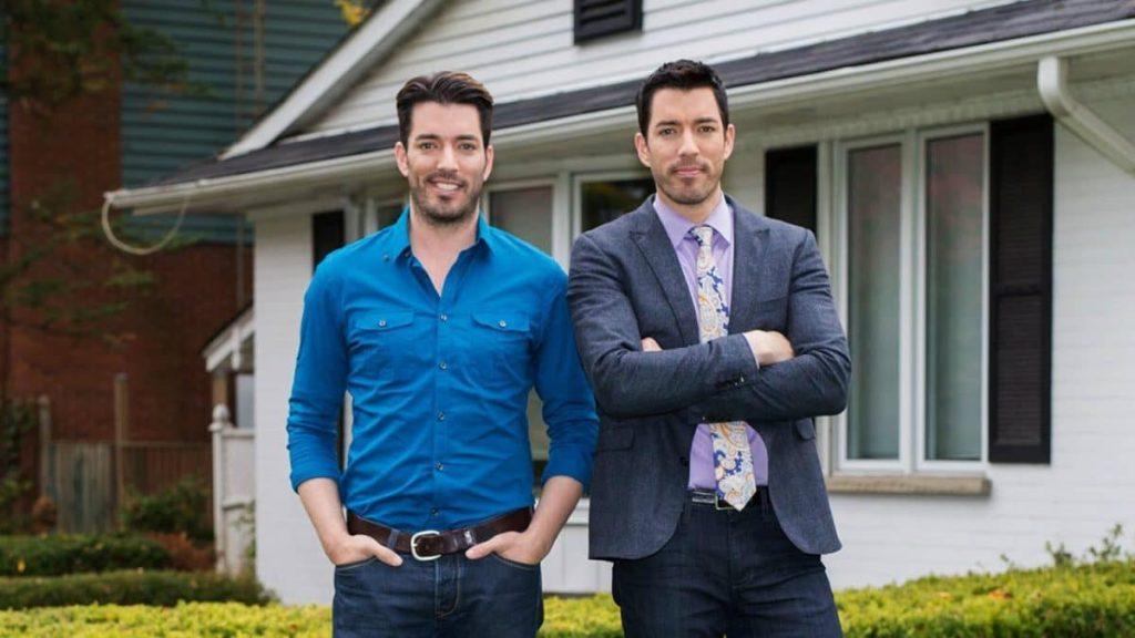 Jonathan e drew scott posam em frente a uma casa no irmãos à obra, programa do discovery h&h