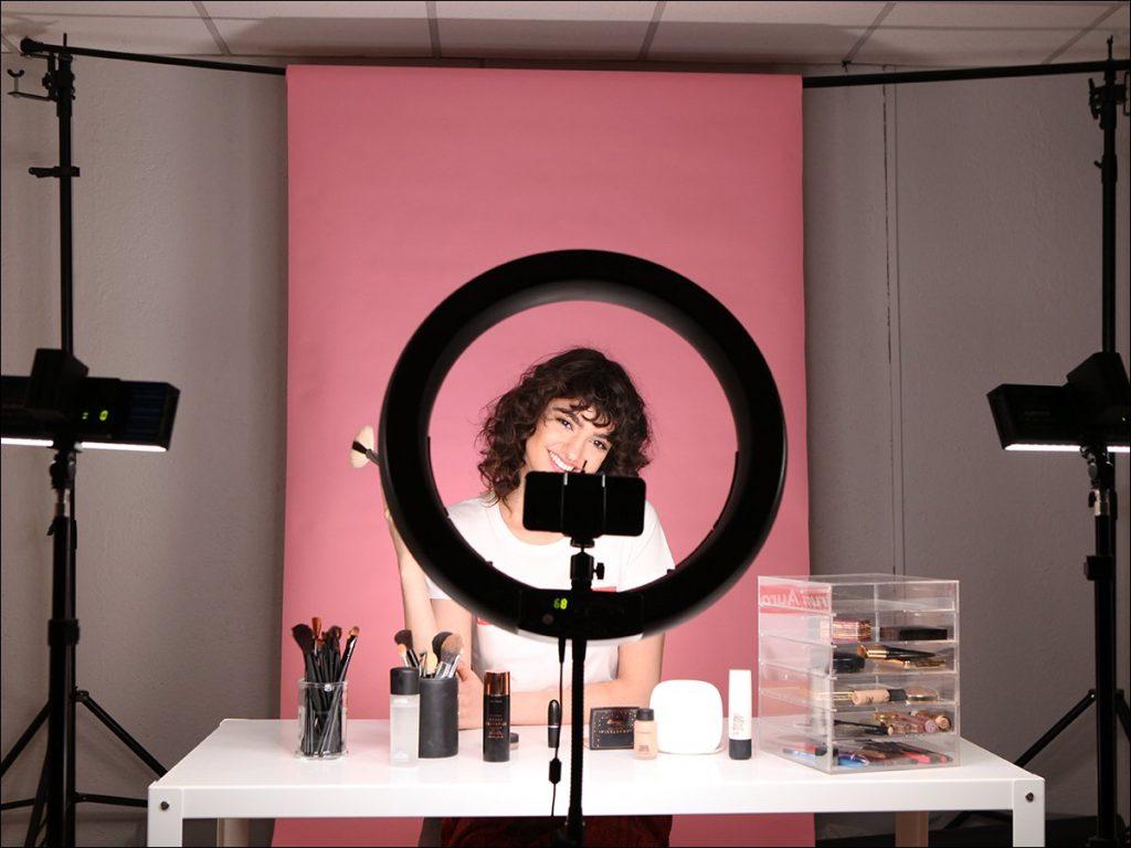 Mulher grava vídeo com luz direto em seu rosto