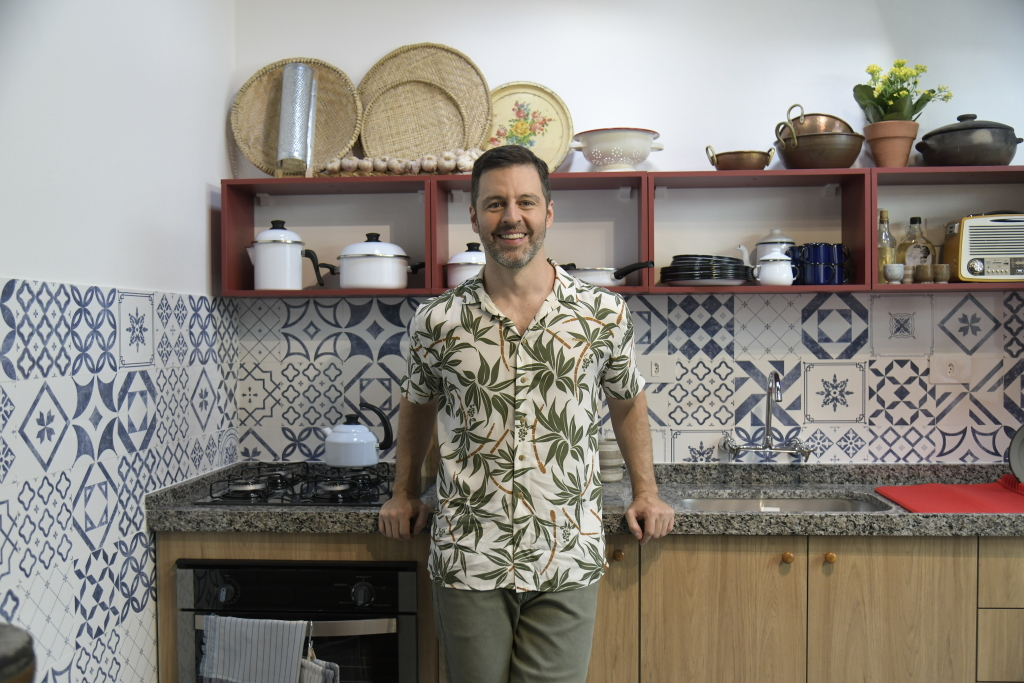 Maurício arruda posa em cozinha, repleta de azulejos brancos e azuis, no programa decora do gnt