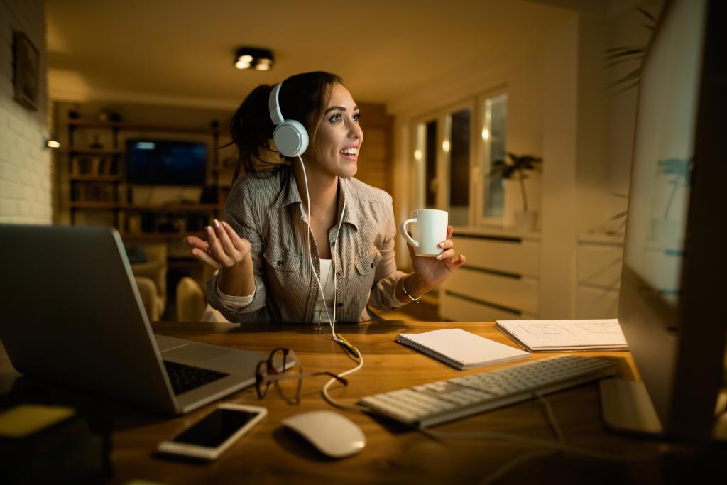 Mulher realiza videoconferência com fone de ouvido frente à uma mesa