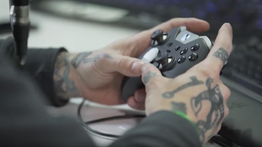 Mãos tatuadas seguram controle de xbox one, parte de vídeo de canal do youtube