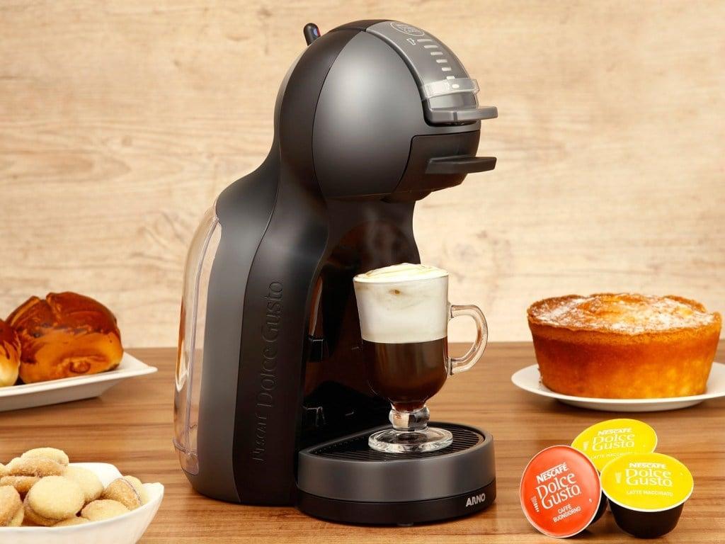 Cafeteira Dolce Gusto Mini Me disposta sobre uma mesa com suas cápsulas no Zoom