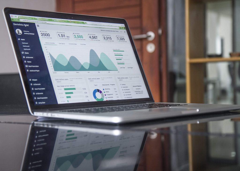 Computador com números e gráficos (Analista de negócios)