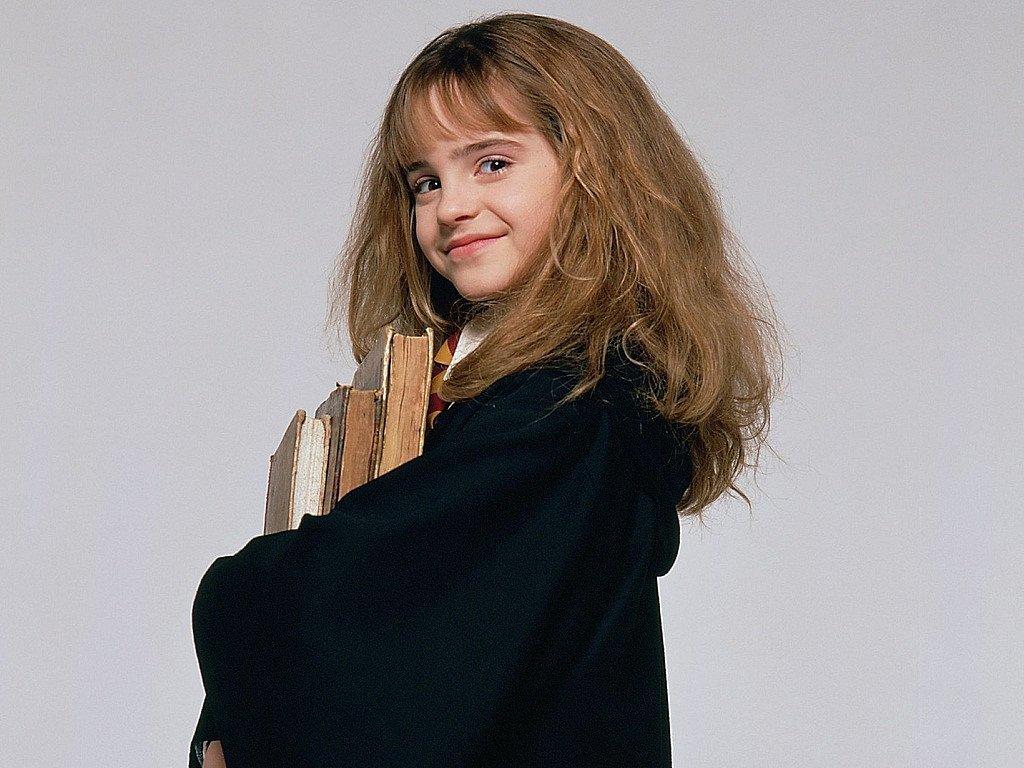 Hermione granger sorri com livro frente a fundo cinza