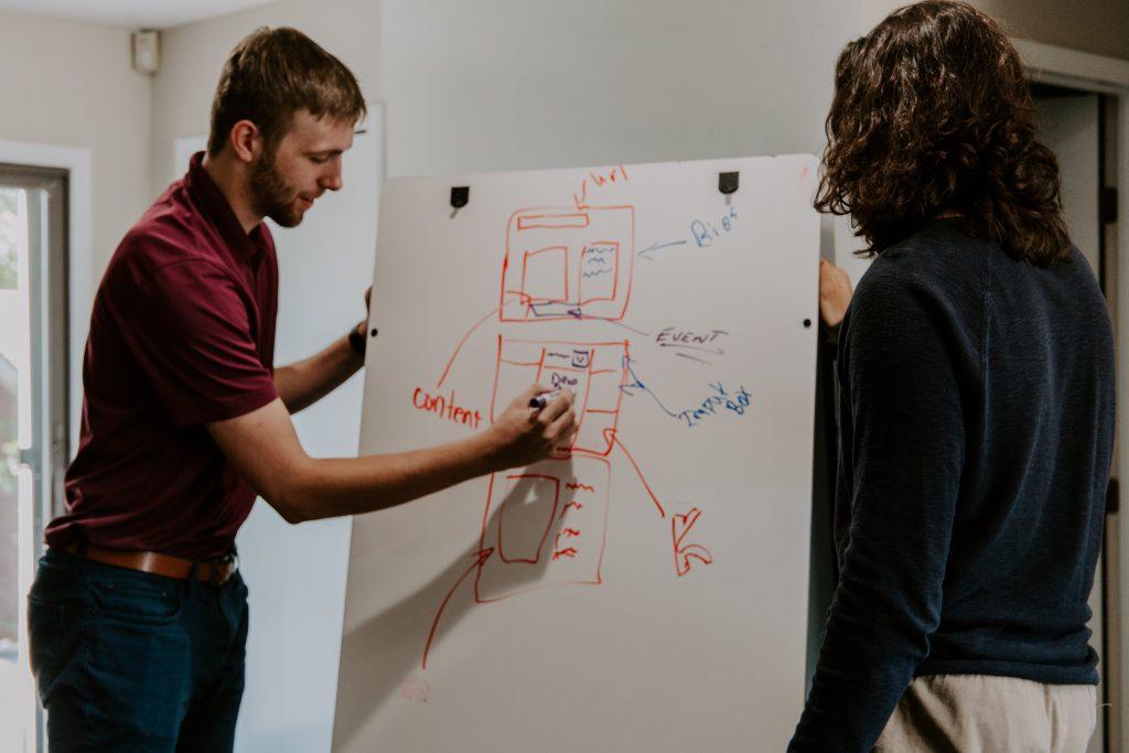 Duas pessoas conversando sobre um projeto (Analista de negócios)