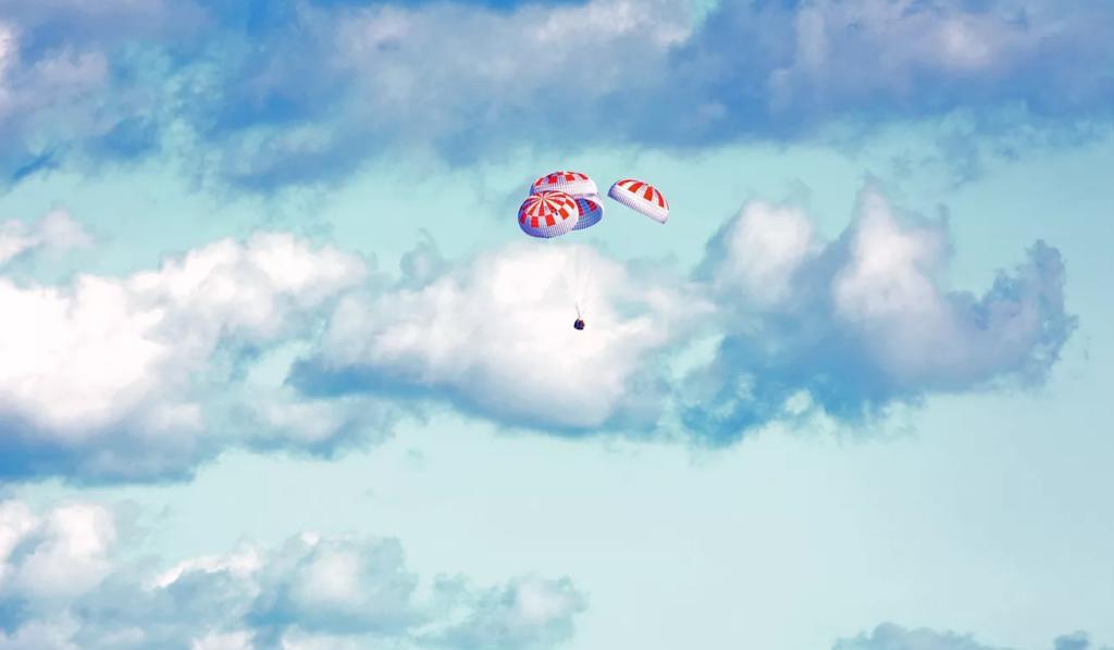 Cápsula crew dragon com paraquedas ativados retornando à terra