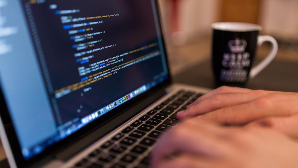 Pessoa digita em um notebook. À esquerda, uma tela de monitor ilumina o ambiente. A tela de um computador é o componente que mais gasta energia em qualquer aparelho eletrônico.