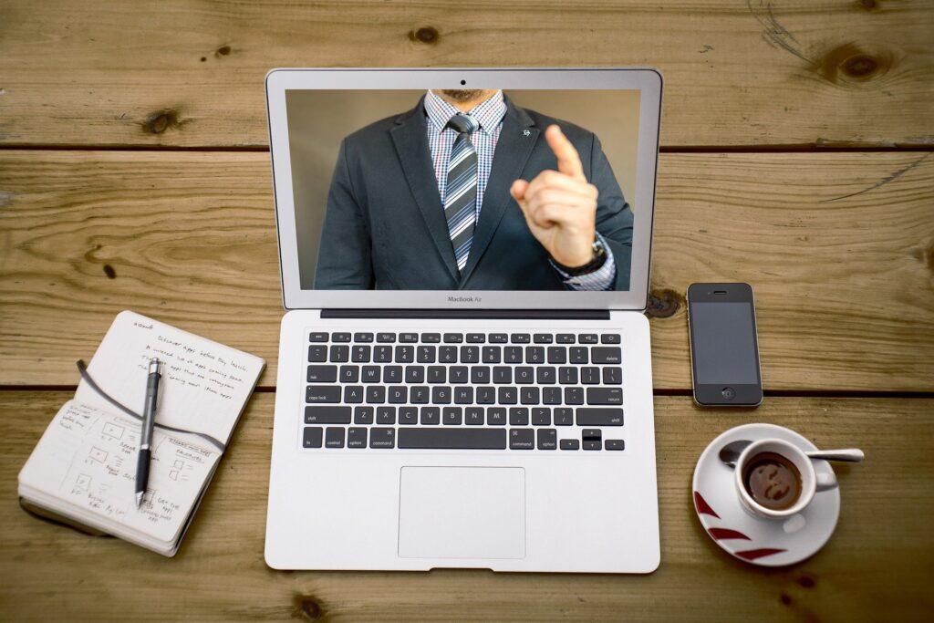 Notebook prateado em cima de uma mesa de madeira com um caderno, um smartphone e uma xícara de café mostrando uma vídeo conferência de um homem com terno e gravata azuis