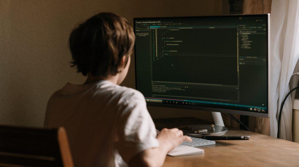 Um garoto de 12 anos com camisa branca sentado numa cadeira de madeira usando o computador numa mesa também de madeira