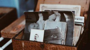 Caixa de madeira com várias fotos antigas em preto e branco, como de um bebê, um jovem adulto de bigode