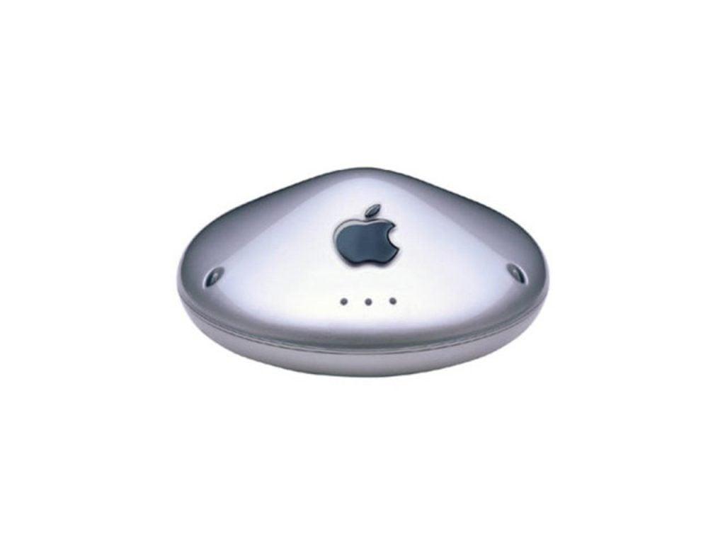Fundo branco. Apple airport graphite visto ao centro. Ele tem cor prata em formato cônico com logo da apple ao centro.