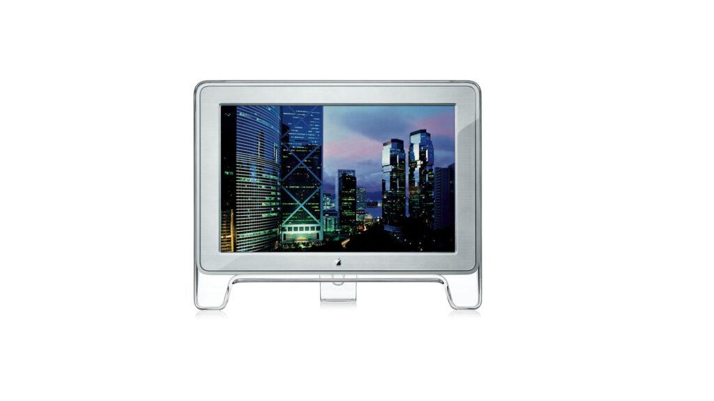 Fundo branco. Ao centro, o apple cinema display. Sua tela é envolta por uma moldura de plástico de alta densidade em um suporte tipo cavalete.