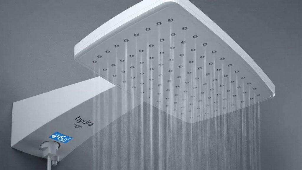À esquerda, chuveiro branco pendurado em parede cinza jorrando água. Ele possui um visor led em sua parte inferior.