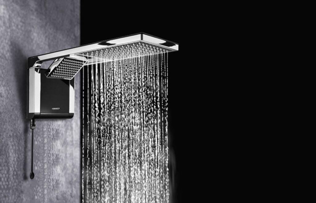 Fundo preto. À direita, chuveiro em metal com formato espalhador de água