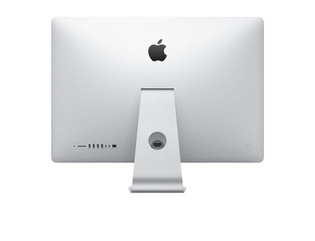 Parte de trás do imac de 27 polegadas, toda branca com o símbolo da apple, uma maçã comida, cinza, na parte superior, e conectores de diversos modelos para fios