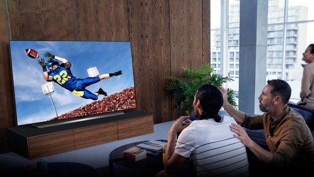 Pessoas assistindo jogo de futebol americano numa das novas tvs oled da lg