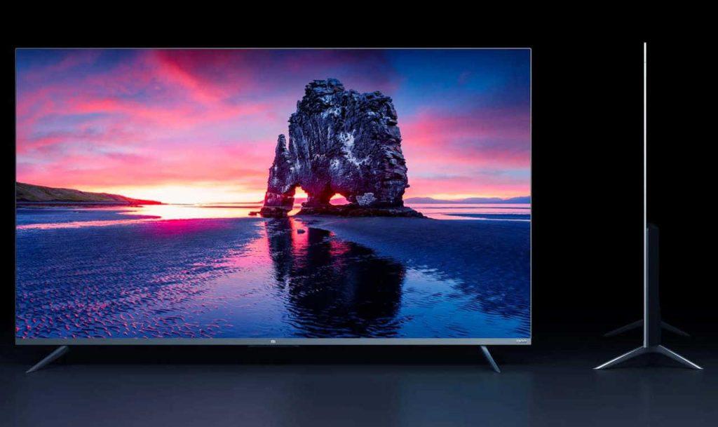 Duas tvs oled em ambiente escuro. À esquerda, tv vista de frente com foto de paisagem contrastante. À direita, tv vista de lado, com sua espessura fina em evidência.