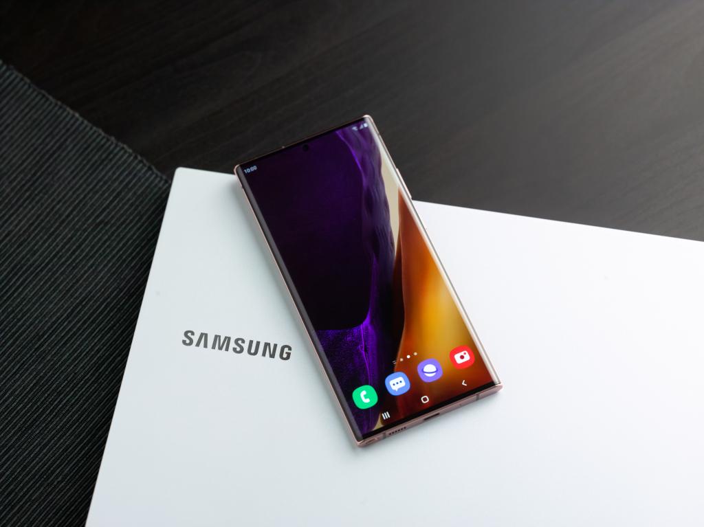 Galaxy note 20 ultra virado para cima, colocado em cima de uma caixa branca da samsung que por sua vez está sobre uma mesa preta