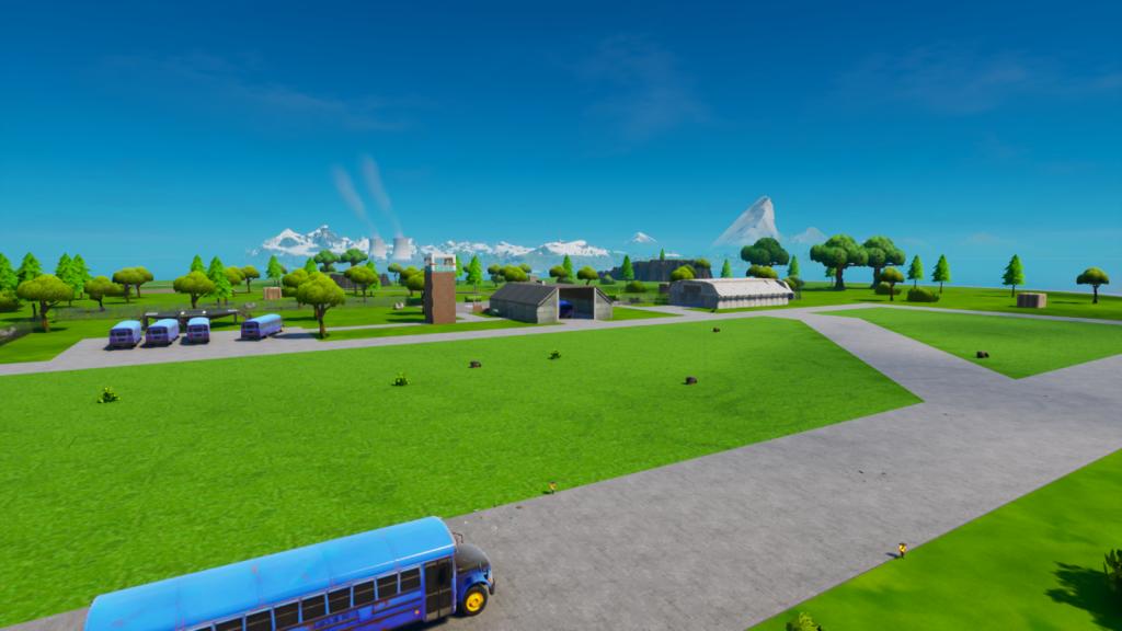 Visão panorâmica da ilha de spawn do fortnite, com o ônibus de batalha na parte inferior e os galpões clássicos na parte de de trás da imagem