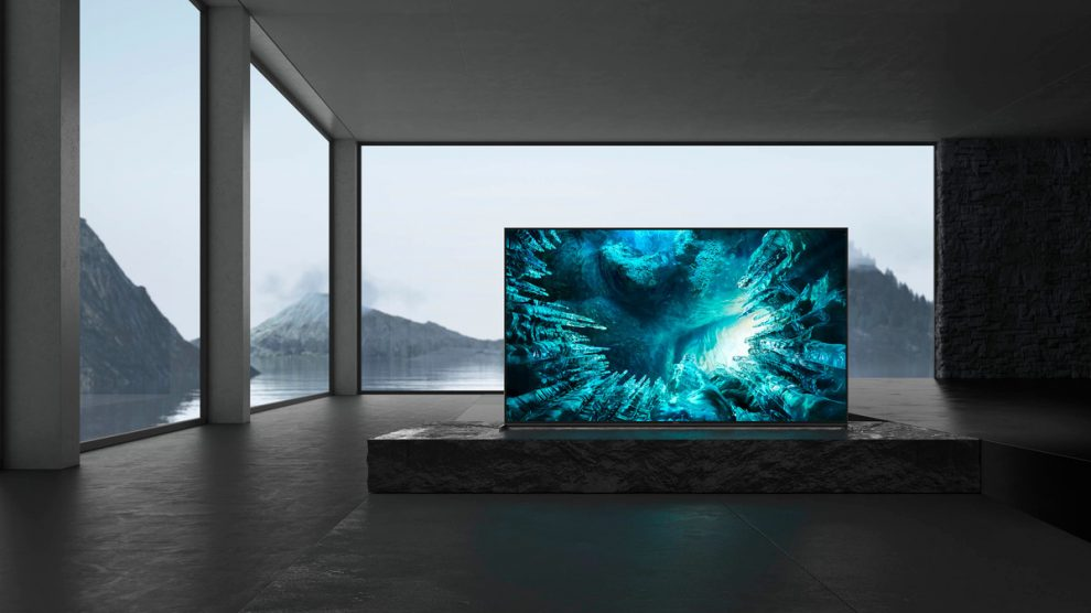 TV 8K da Sony, Z8H, posicionada numa casa com paredes cinzentas, em cima da mesa do que parece ser uma sala