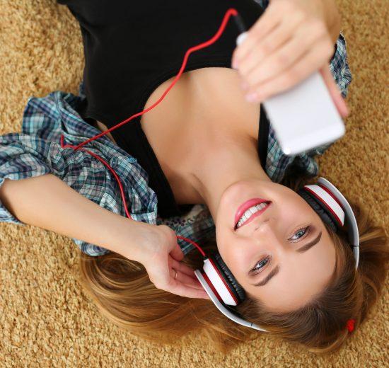 Moça loira lendo como baixar vídeos no Youtube no celular