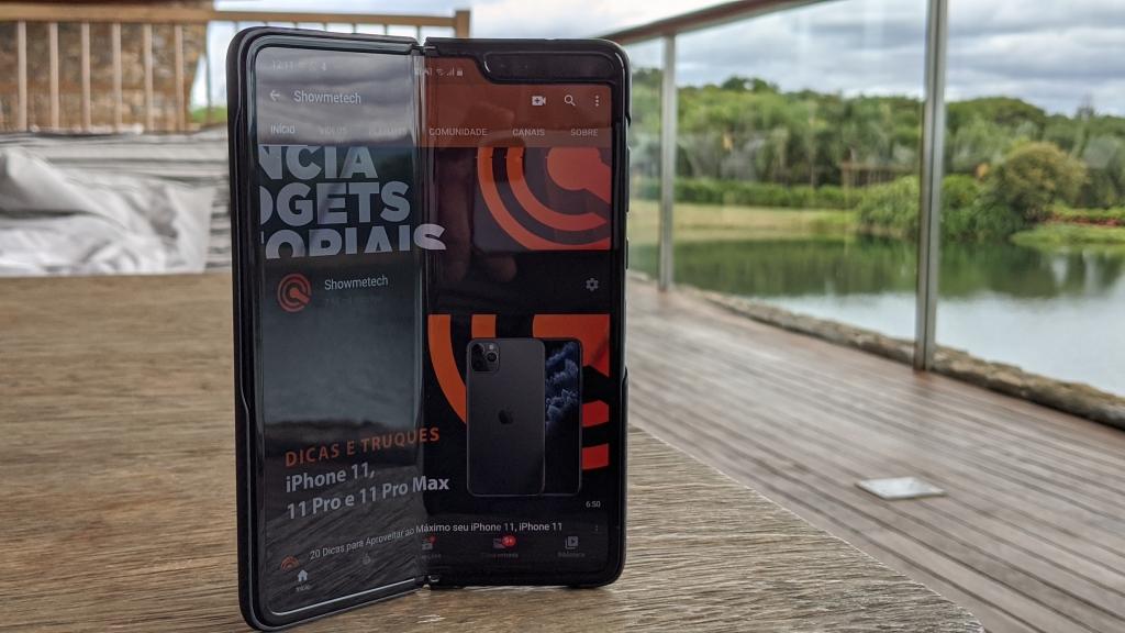 O primeiro exemplo de smartphones dobráveis da Samsung, o Galaxy Fold está aberto numa página do Showmetech sob uma mesa de madeira