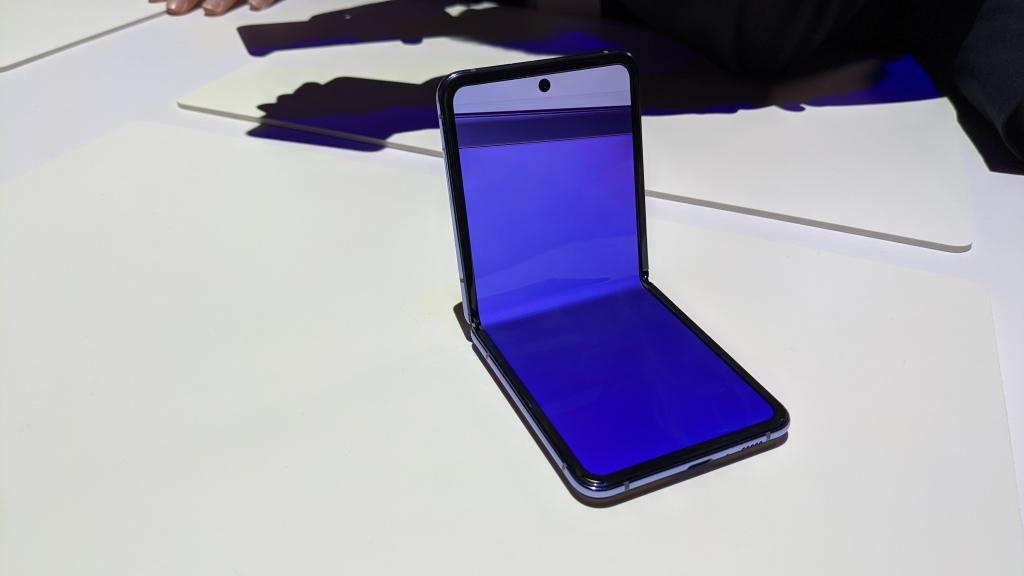 Galaxy Z Flip, segundo dos smartphones dobráveis da Samsung, em cima de uma mesa branca, com metade da tela levantada