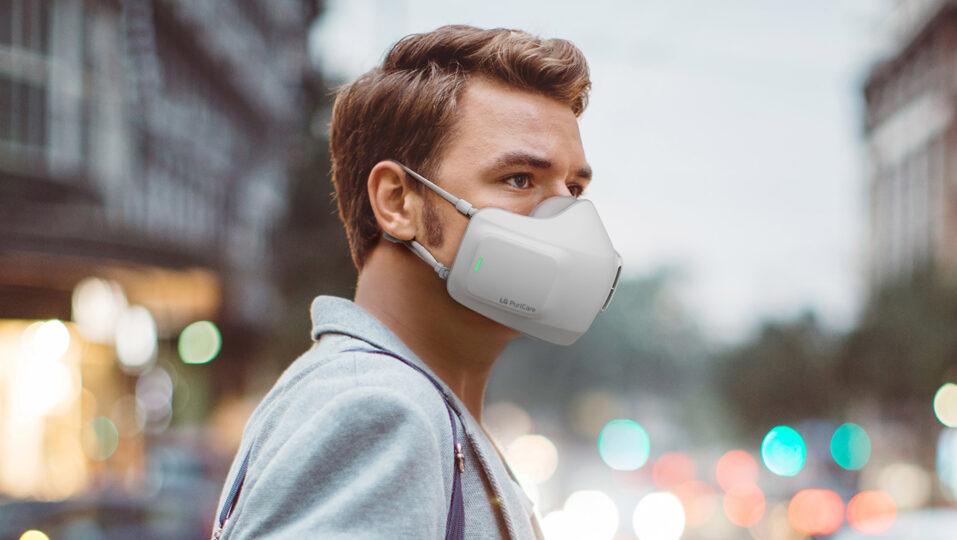 Homem branco de cabelo castanho usando o puricare wearable air purifier da empresa lg, que é uma máscara com purificadores de ar dentro