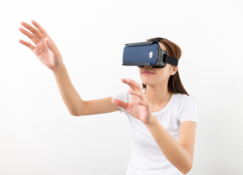 A realidade virtual ilustrada com uma moça simulando o uso e se divertindo com ela