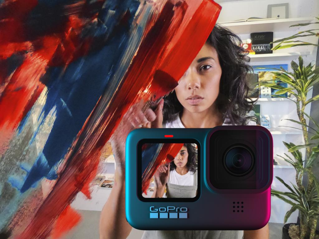 HERO9 Black sendo usada como webcam para filmar uma moça morena de cabelo cacheado e preto pintando a própria câmera de azul e vermelho