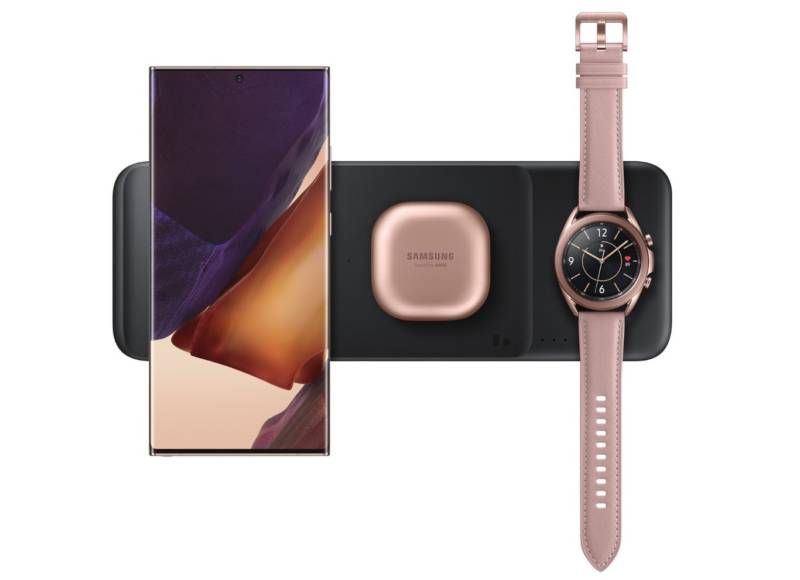 Anunciado no ifa 2020, o wireless charging trio da samsung é uma barra preta com três entradas para três dispositivos. Na imagem, um smartwatch na direita e um celular na esquerda.