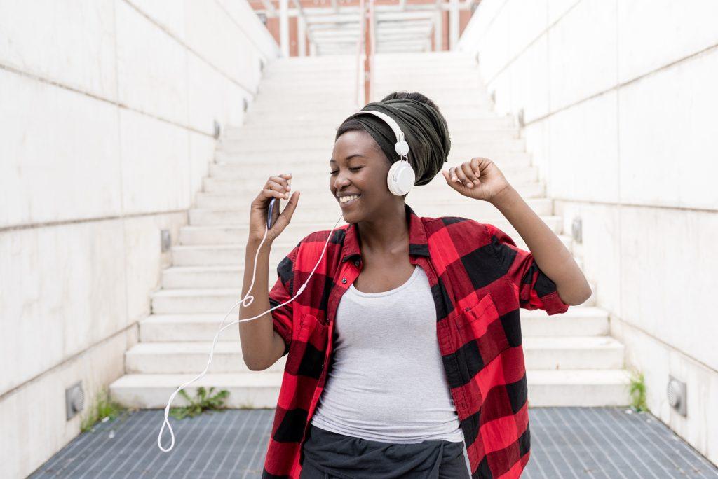 Uma jovem escuta música, se divertindo muito com isso