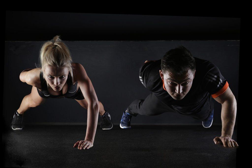 Mulher loira, à esquerda, fazendo flexão e homem moreno, à direita, também fazendo flexão para demonstrar o propósito em manter a saúde em dia.