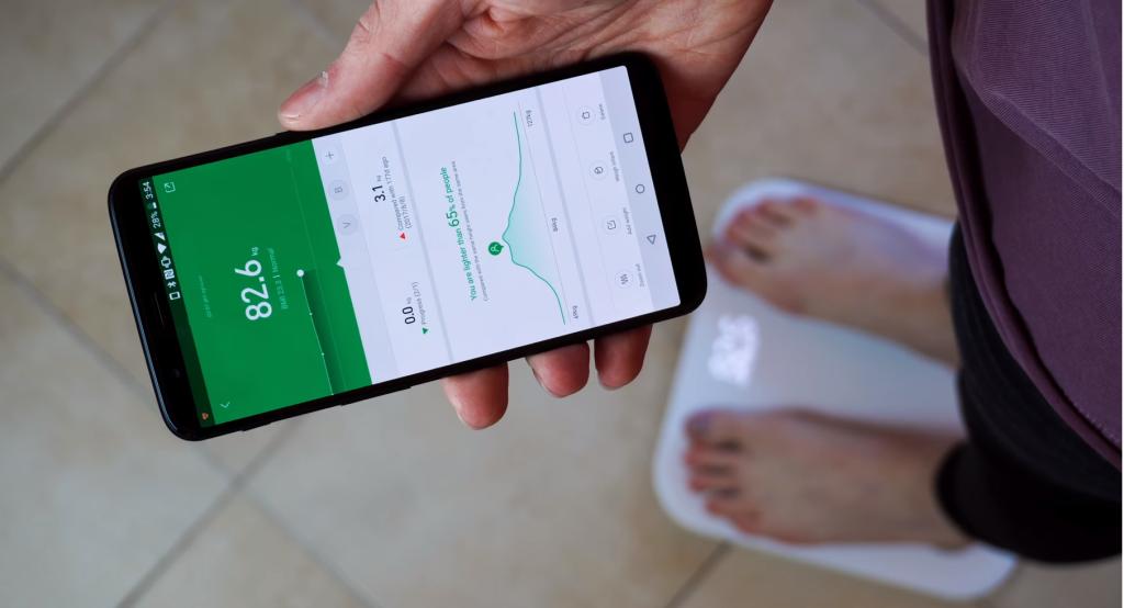 Balança inteligente ligada ao aplicativo no celular, mostrando dados sobre o peso do usuário.
