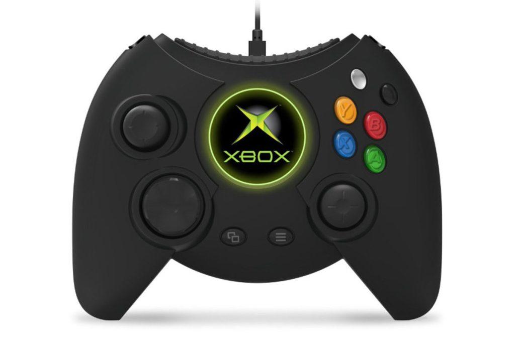 O controle duke está em pé com um fundo branco. O controle é revestido de preto e os botões ao lado direito contém algumas cores, como azul e vermelho. No centro, há o logo da xbox com destaque em verde.