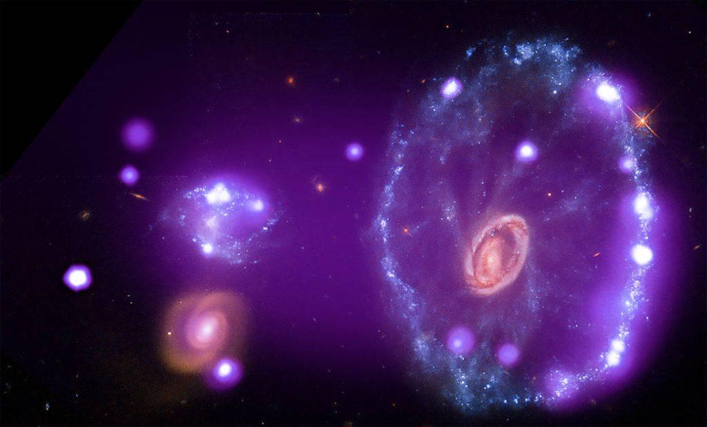 A galáxia cartwheel tem forma parecida a um alvo ou um olho. Em volta, uma grande quantidade de estrelas.