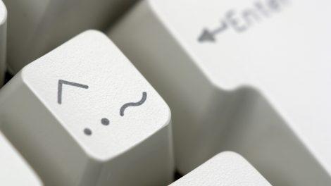 Detalhe de teclas de um teclado bege. Em destaque, tecla com acento circunflexo no canto superior esquerdo. Logo abaixo, à esquerda, dois pontos e à direita, um til.
