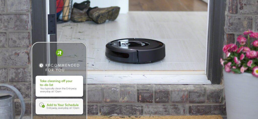 Aspirador robô preto no centro da tela, em cima de uma superfície lisa, limpando o que parece ser o resto de poeira da casa