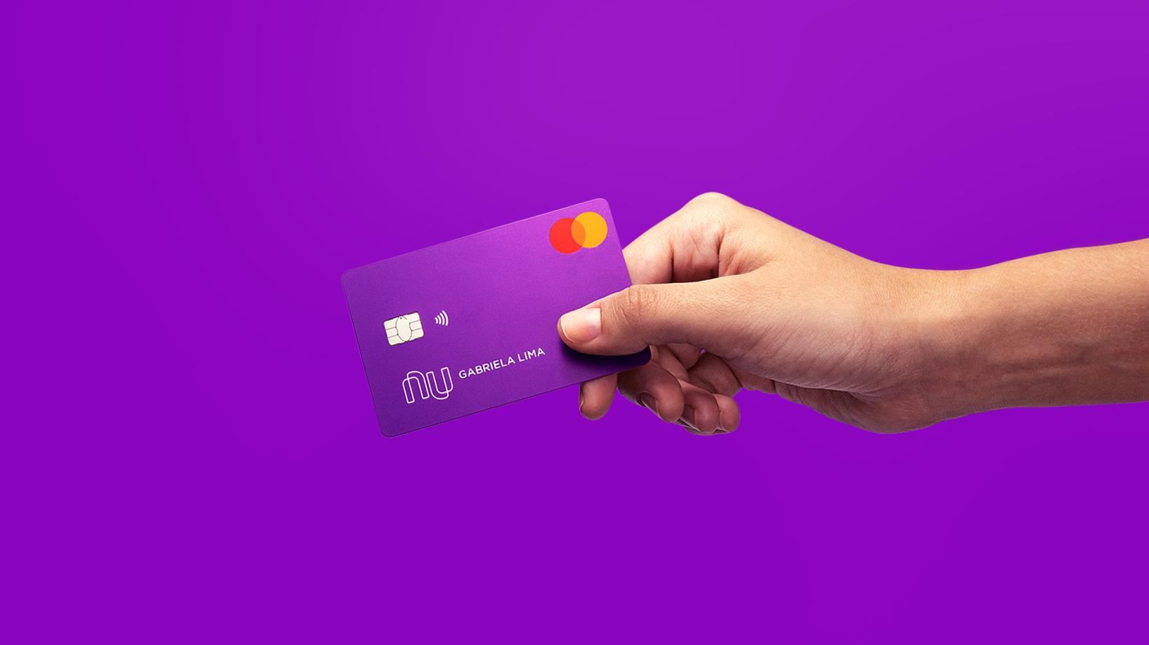 Nubank compra a easynvest, na foto, uma moça segurando um cartão de crédito roxo do nubank sobre um fundo roxo
