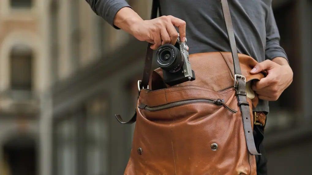 Pessoa guardando a câmera sony a7c na bolsa