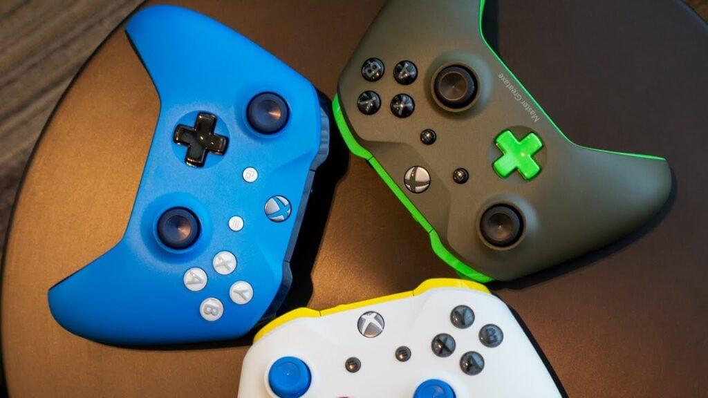 Três controles da versão xbox one s, nas cores azul, branco e verde.