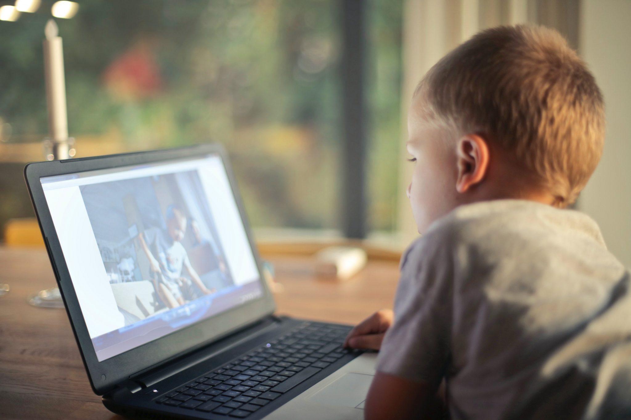 Em imagem, menino navega na internet em seu notebook