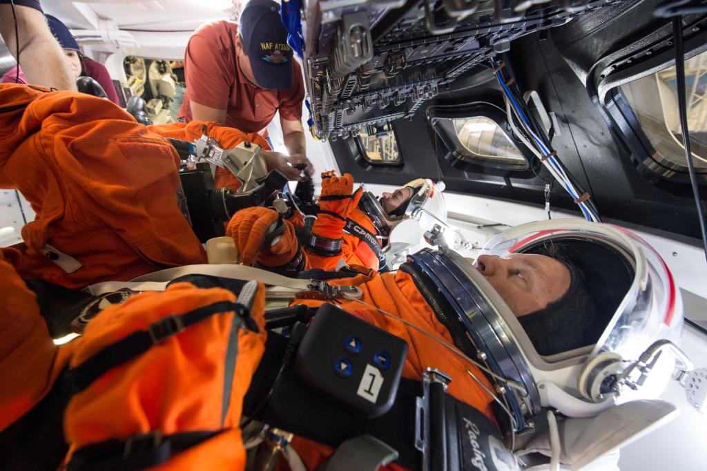 Engenheiros do johnson space center da nasa em houston estão avaliando como as tripulações dentro de uma maquete da espaçonave orion interagem com o controlador de mão rotacional e o dispositivo de controle do cursor dentro de seus trajes espaciais modified advanced crew escape.