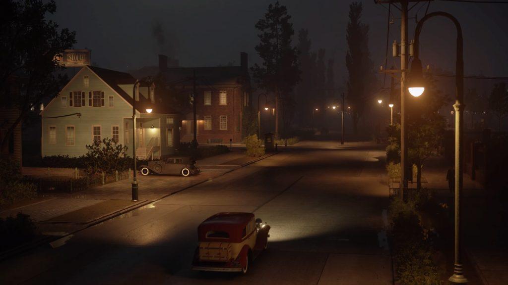 Vista aérea de um carro se aproximando de casas à noite.