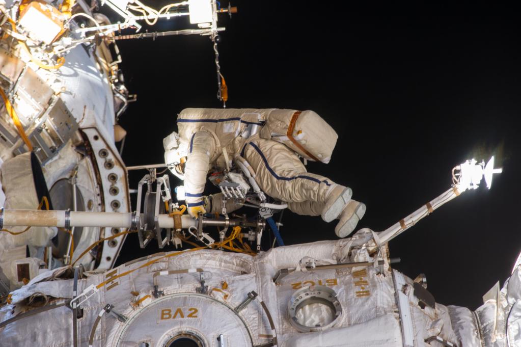 Trajes espaciais protegem um astronauta russo que está fazendo reparos nas câmeras externas da estação espacial internacional