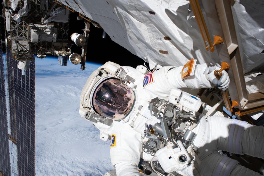 Vista do traje espacial do astronauta andrew morgan enquanto ele mexe numa estrutura da estação espacial