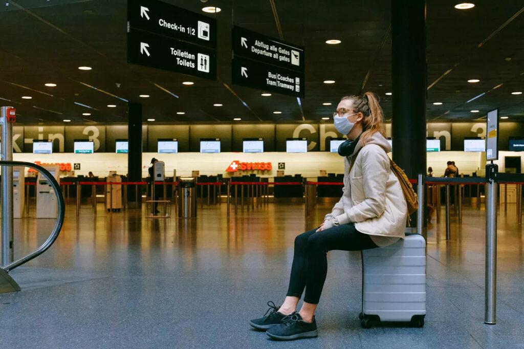 Mulher sentada no aeroporto de máscara